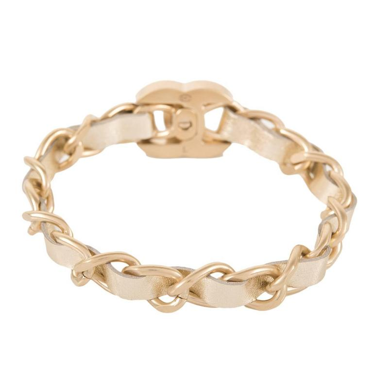 Chanel bracelet of gold metallic leather interwoven with matte gold tone chain link with iconic CC-logo at front and turn lock closure.  Collection: 16V (2016 collection)  Condition: Pristine; never worn  Accompanied By: Chanel box, dustbag,