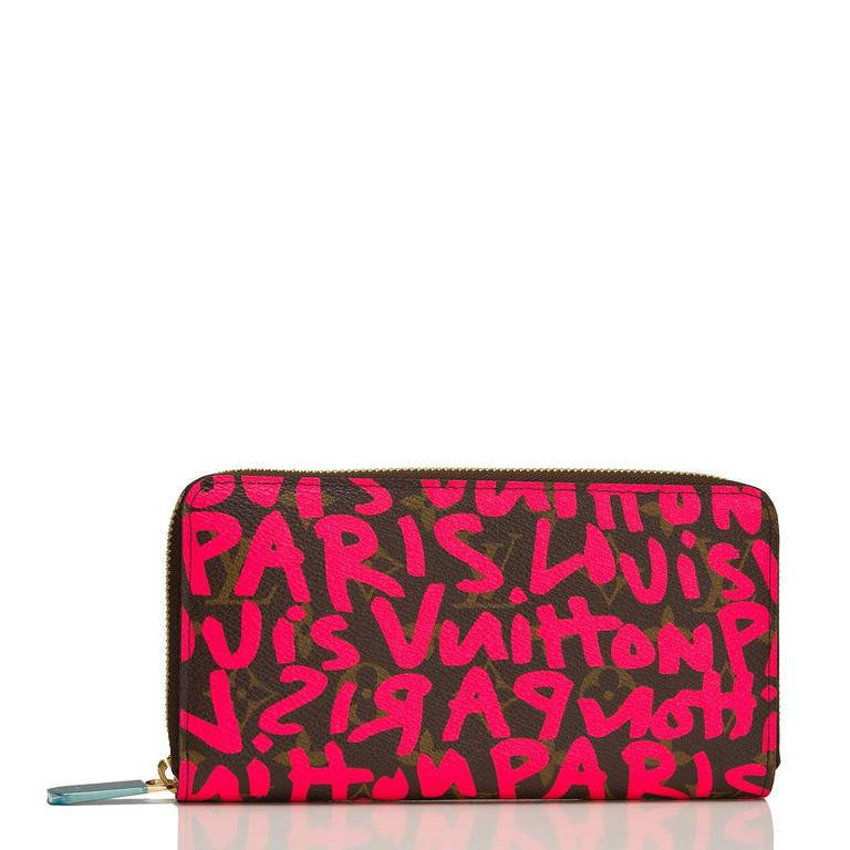 """Louis Vuitton limited edition Stephen Sprouse Monogram Graffiti Zippy Wallet of coated canvas with all over """"Louis Vuitton Paris"""" in neon fuchsia pink.  This wallet has a 3/4 wrap around zipper that opens to a fuchsia, cross-grain leather compact"""