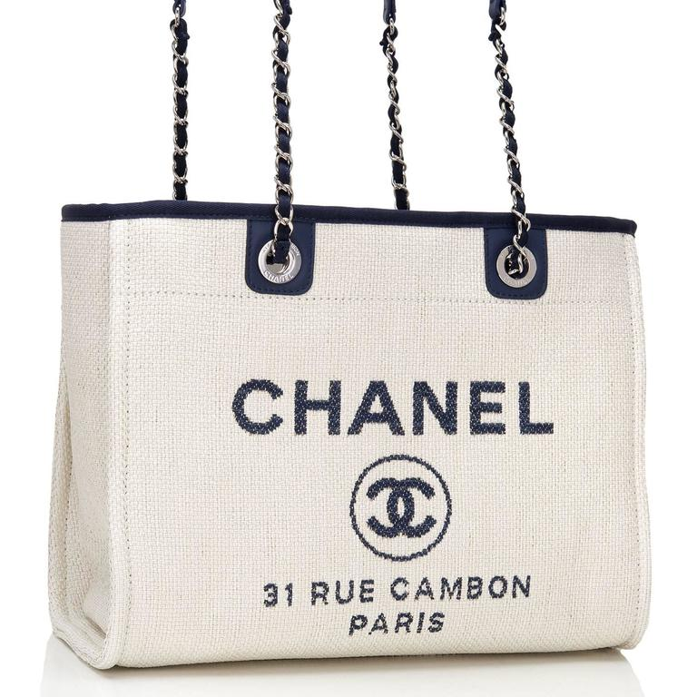 """Chanel Small Deauville Canvas Tote of white canvas, navy leather trim and silver tone hardware.  This bag features the signature CC logo in a circle with the brand CHANEL above it and the Paris flagship store address -- """"31 Rue Cambon Paris"""" --"""
