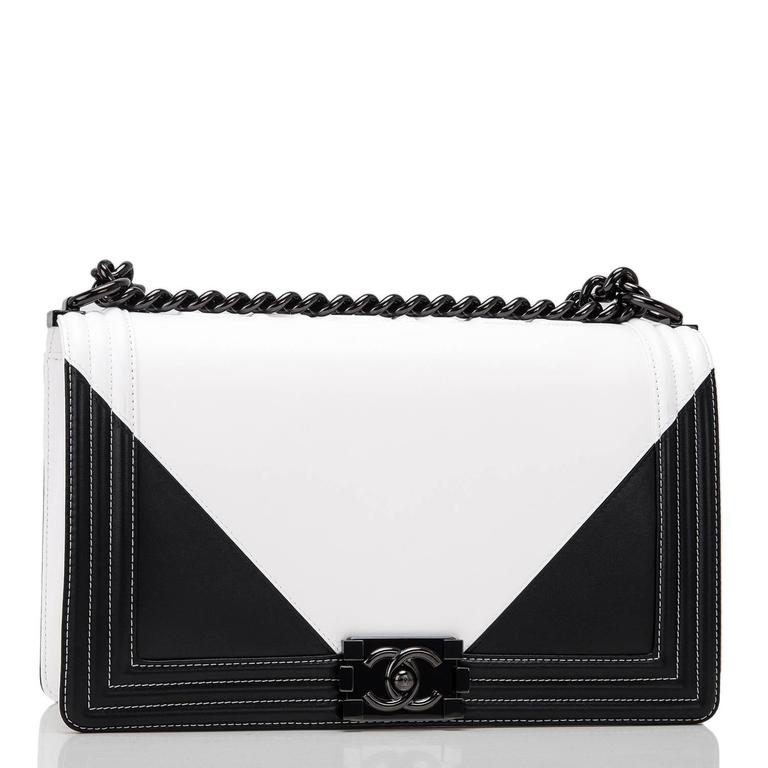 Chanel New Medium Boy bag of black and white lambskin leather and black hardware.  This Chanel bag is in the Boy style with a full front flap with the Boy signature CC push lock closure, white stitching, smooth leather trim and black metal chain