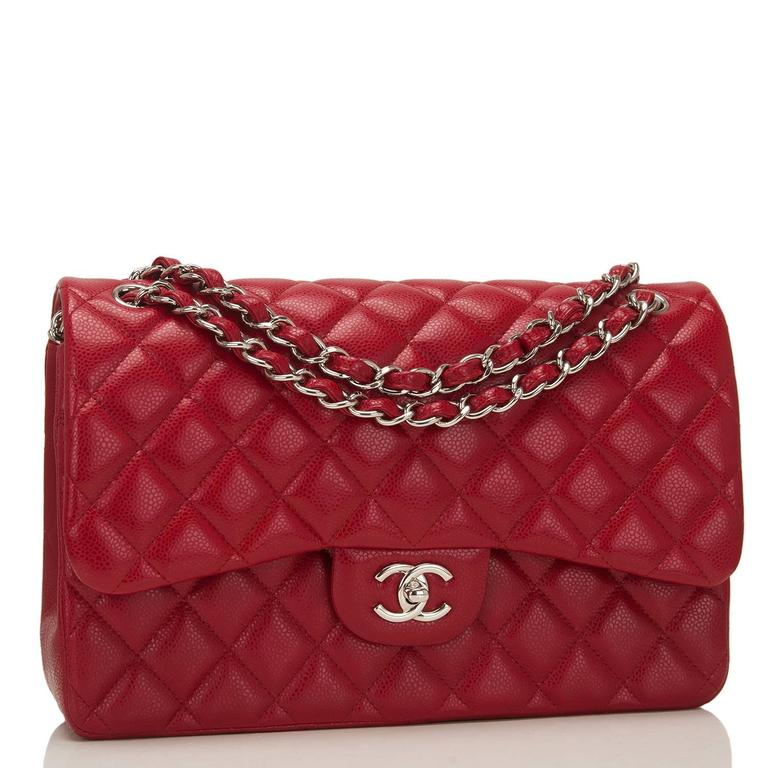 Chanel Jumbo Classic double flap bag of red caviar leather with silver tone hardware.  This bag features a front flap with signature CC turnlock closure, a half moon back pocket, and an adjustable interwoven silver tone chain link and dark red