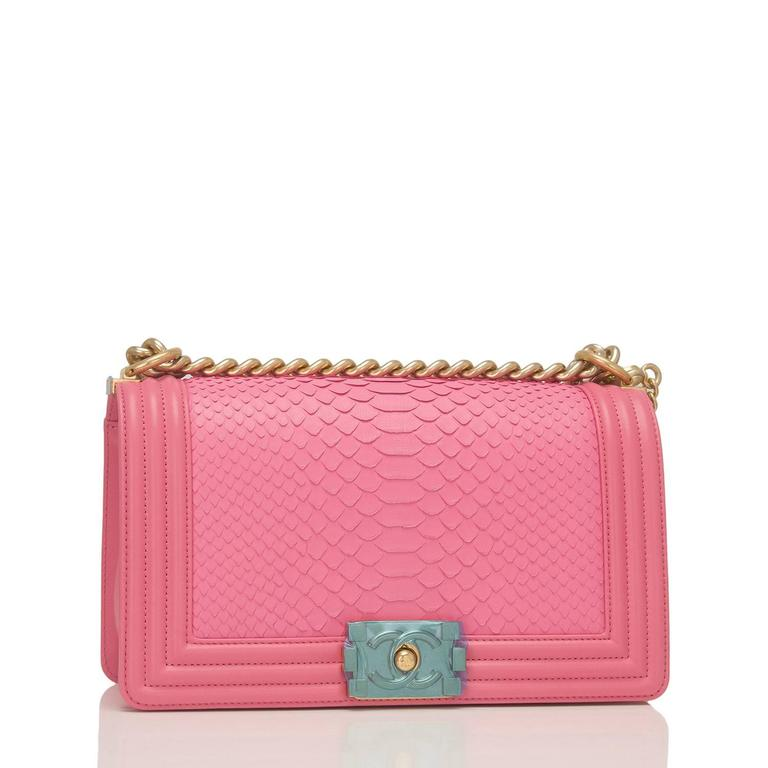 Chanel Medium Boy bag of pink python and gold tone hardware.  This Chanel bag is in the classic Boy style with a full front flap with the Boy signature CC push lock closure detail, lambskin leather accents and gold tone chain link with pink leather