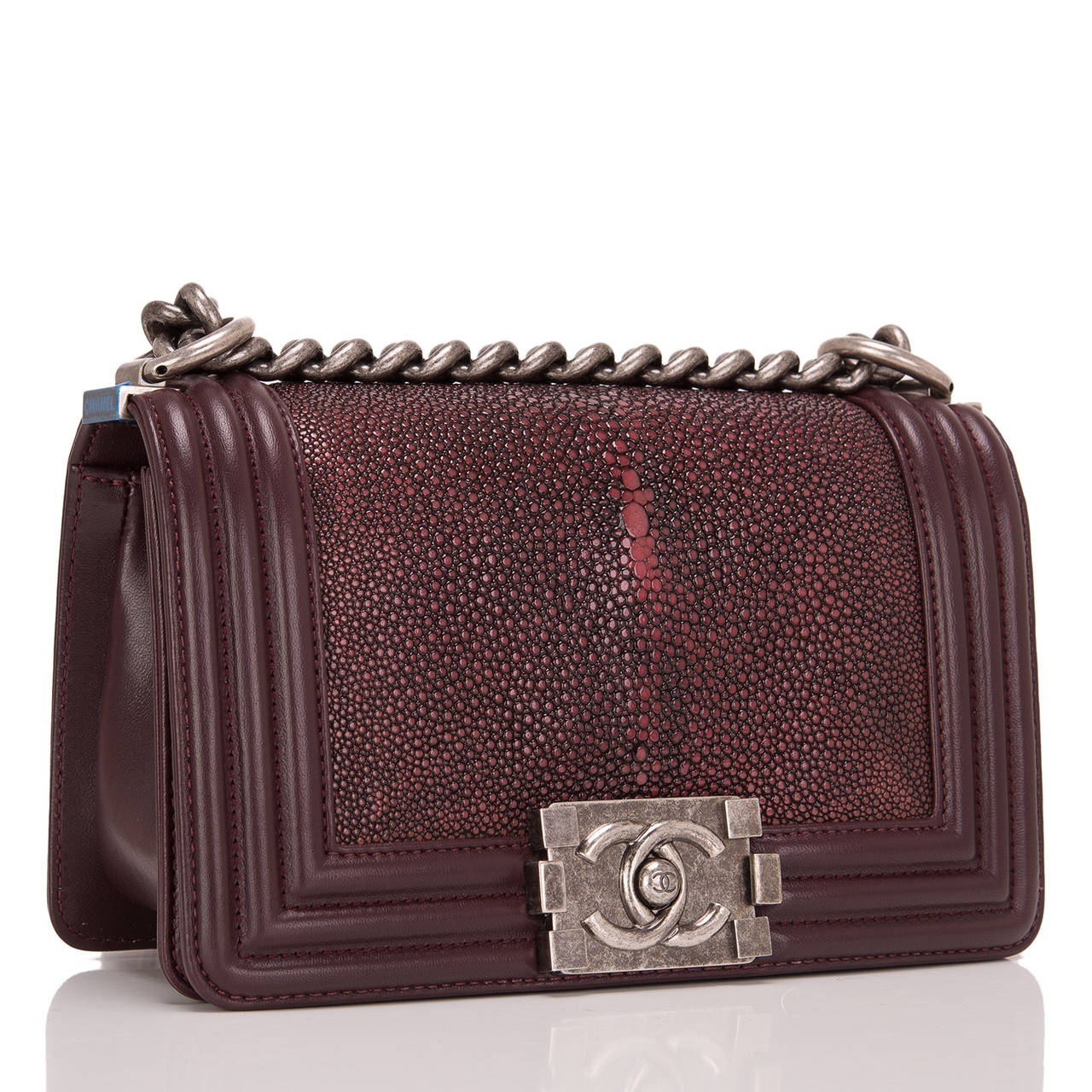This limited edition Small Boy bag is exceptional in burgundy stingray, accented by burgundy lambskin leather and aged ruthenium hardware. The bag has a full front flap with the Boy Chanel signature CC push lock closure and aged ruthenium chain link