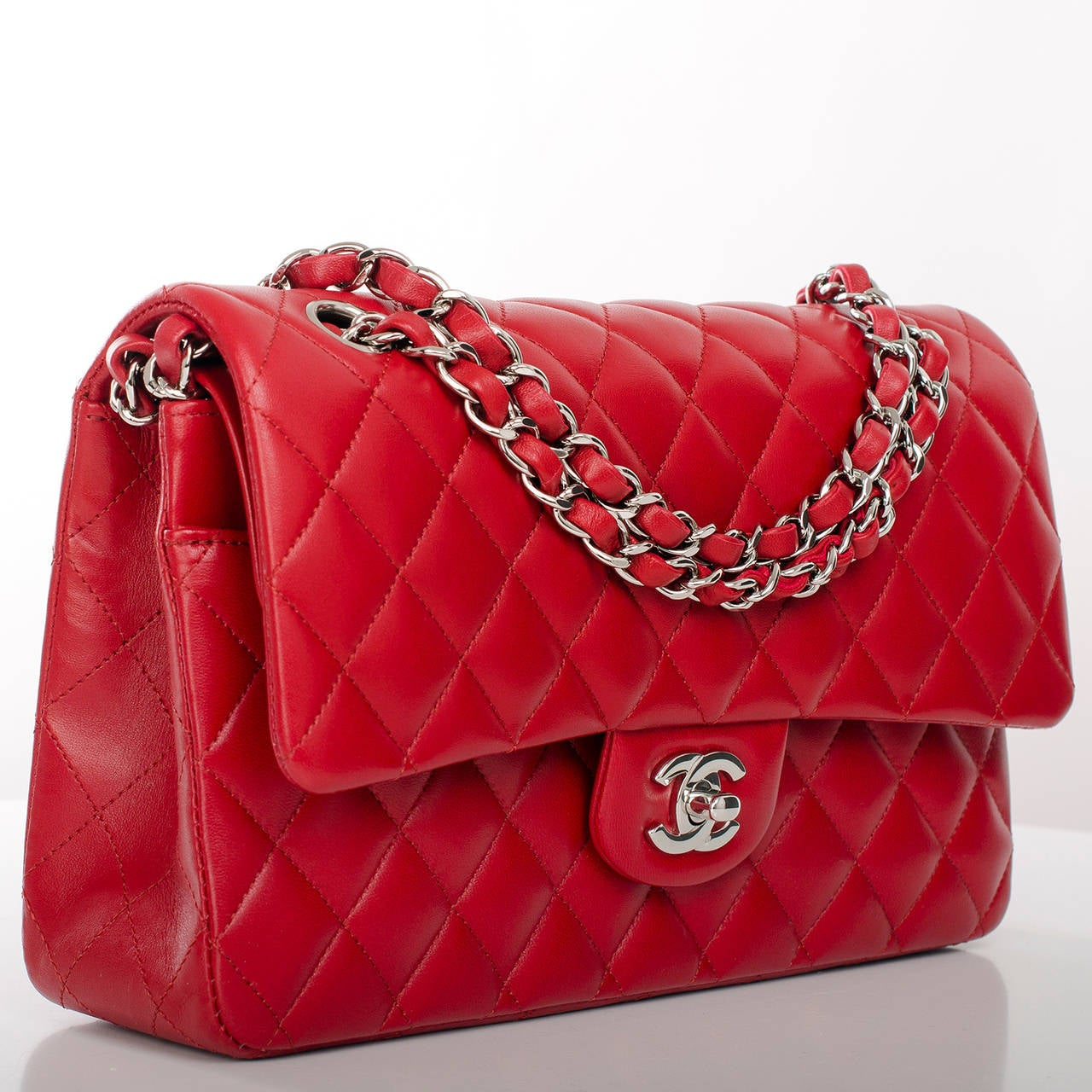 This Medium Classic double flap bag marries red quilted lambskin leather with silver tone hardware and features a full front flap with signature CC turnlock closure, half moon back pocket and an adjustable interwoven silver tone chain link and red