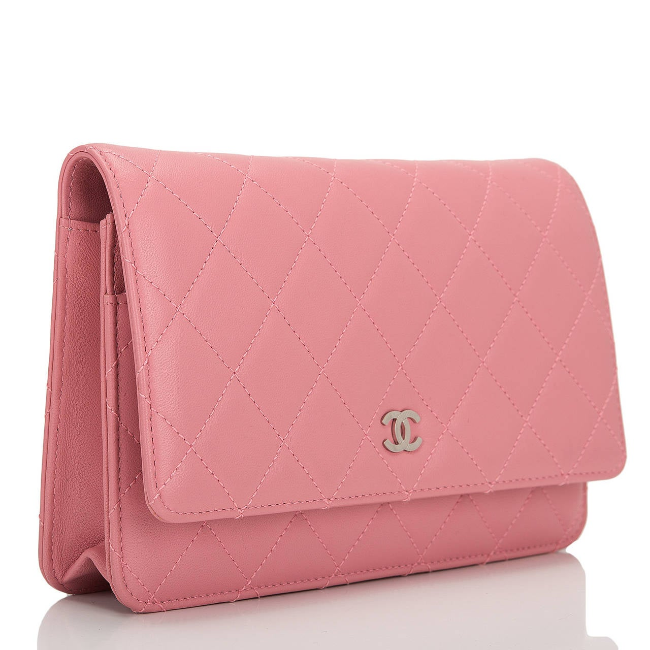Chanel blush pink Classic Wallet On Chain (WOC) of quilted lambskin leather with silver tone hardware.  This Wallet On Chain features signature Chanel quilting, a front flap with CC charm and hidden snap closure, a half moon rear pocket and an