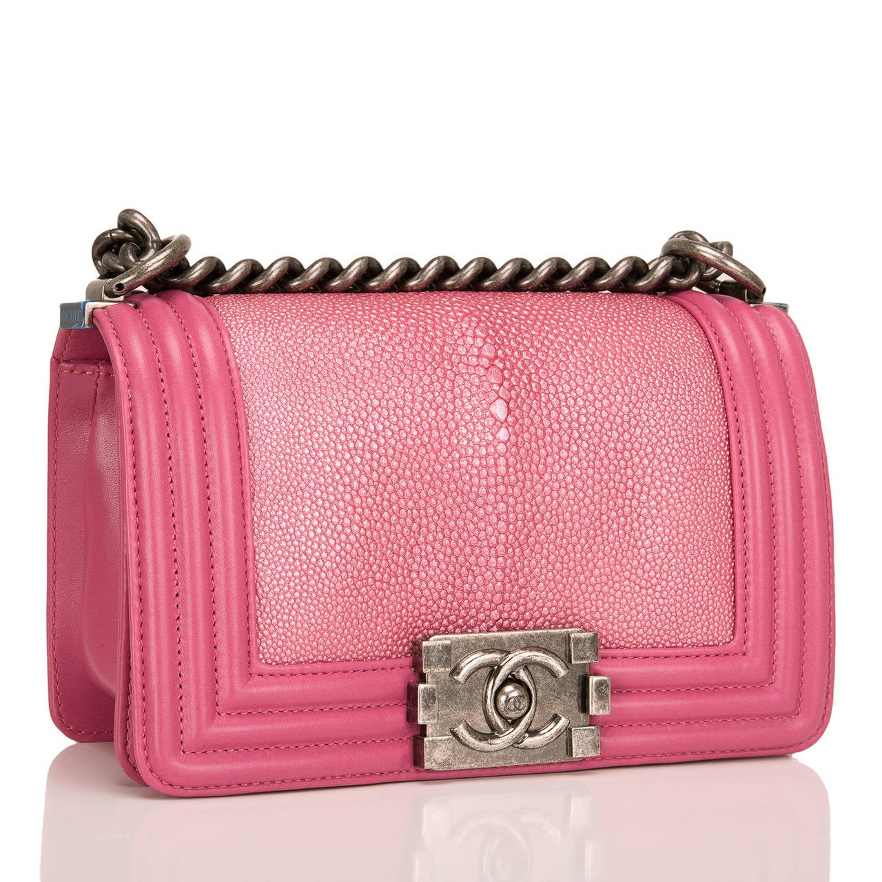 This limited edition Small Boy bag is exceptional in metallic pink stingray, accented by pink lambskin leather and aged ruthenium hardware. The bag has a full front flap with the Boy Chanel signature CC push lock closure and aged ruthenium chain