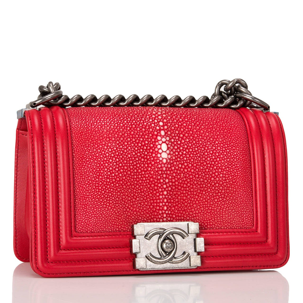 This limited edition Small Boy bag is exceptional in red stingray, accented by red lambskin leather and aged ruthenium hardware. The bag has a full front flap with the Boy Chanel signature CC push lock closure and aged ruthenium chain link and red