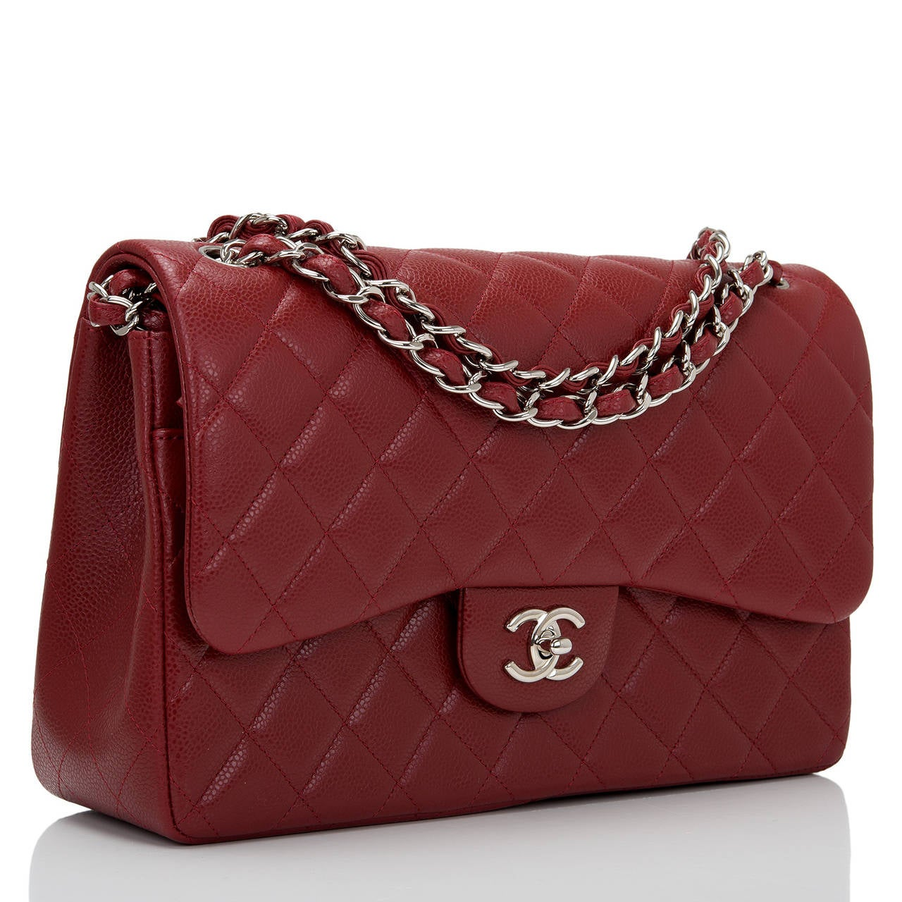 Chanel Jumbo Classic double flap bag of dark red caviar leather with silver tone hardware.  This bag features a front flap with signature CC turnlock closure, a half moon back pocket, and an adjustable interwoven silver tone chain link and dark