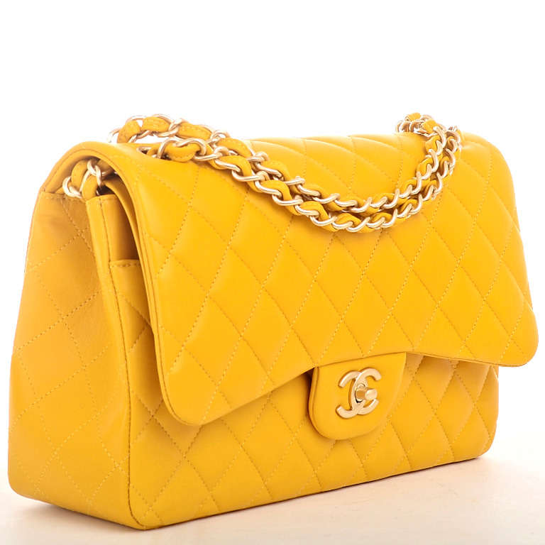 Chanel yellow Jumbo Classic double flap bag of quilted lambskin leather with matte light gold tone hardware.  This limited edition Jumbo Classic double flap bag of yellow quilted lambskin leather with gold tone hardware features a front flap with