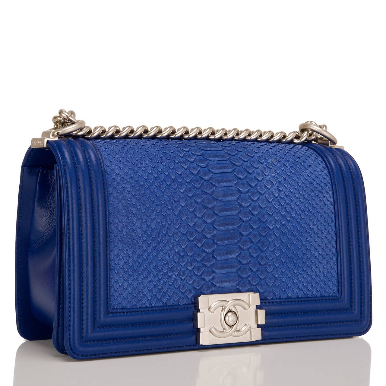 This Chanel blue python Medium Boy bag features beautiful blue python skin and matte silver tone hardware with blue lambskin trim. This Chanel bag is in the classic Boy style with a full front flap with the Boy signature CC push lock closure detail