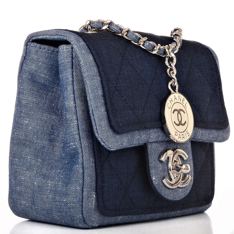 Chanel Denim Graphic Small flap bag featuring quilted indigo denim on blue denim body with silvertone hardware, front flap with CC turnlock closure and interwoven silvertone chain link and denim shoulder/crossbody strap with dangling Chanel CC