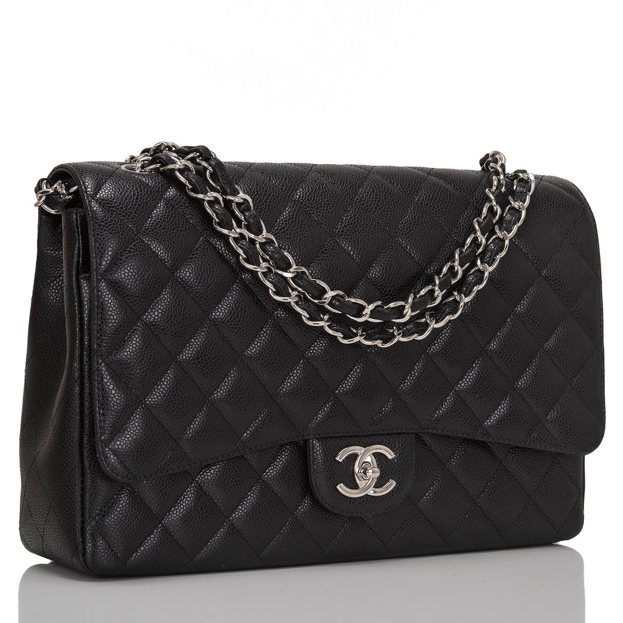 Chanel Maxi Classic double flap of black quilted caviar leather with silver tone hardware features a front flap with signature CC turnlock closure, a half moon back pocket, and an adjustable interwoven silver tone chain link and black leather