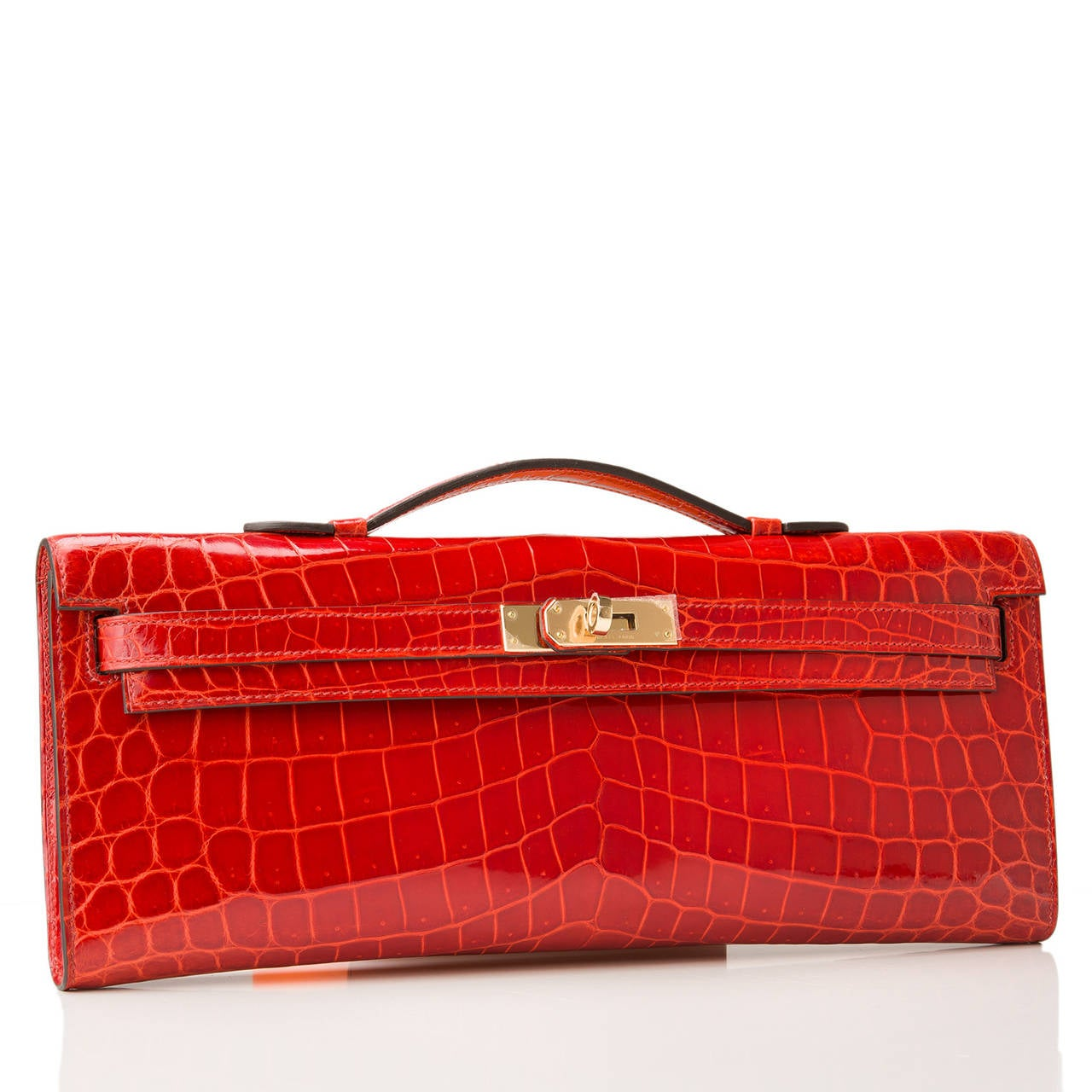 Hermes Sanguine shiny porosus crocodile Kelly Cut with permabrass hardware.  This Kelly Cut in a Hermes' favorite color -- Sanguine -- is a gorgeous red that is elegant with rare Porosus crocodile skin and gold hardware; the bag has tonal