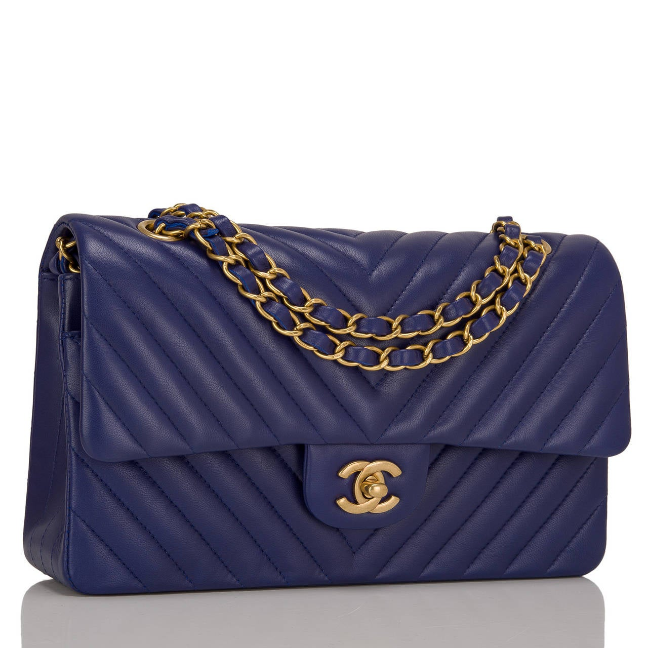 This limited edition Chanel Blue Chevron Medium classic double flap bag in blue lambskin leather and aged gold tone hardware is an edgy take on the iconic Chanel Classic bag. It features a front flap with signature CC turnlock closure, half moon