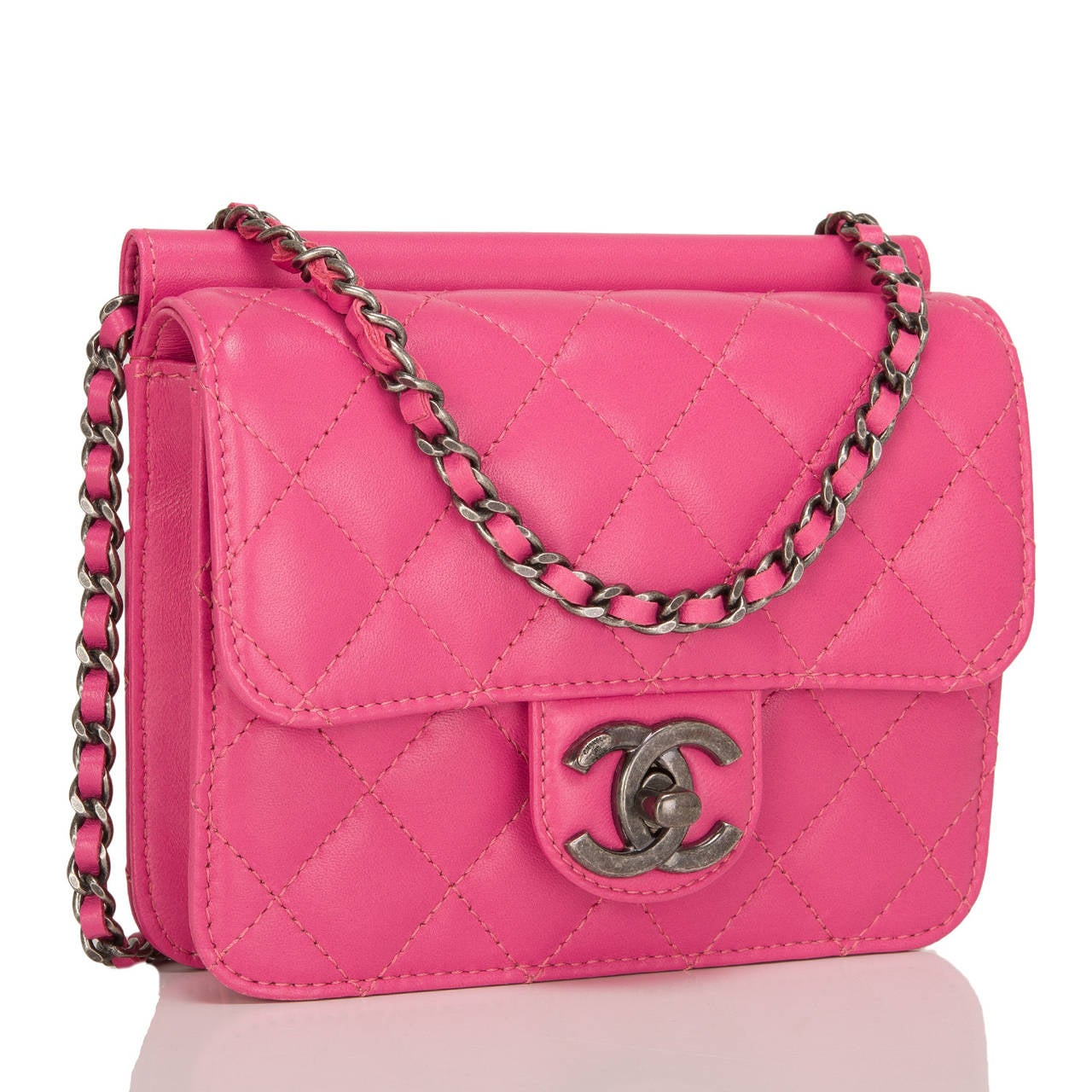 This Chanel Crossing Times Mini Flap bag in pink quilted lambskin leather with aged ruthenium hardware features a front flap and with CC turnlock closure, half moon back pocket and interwoven chain link and pink leather shoulder/crossbody.
