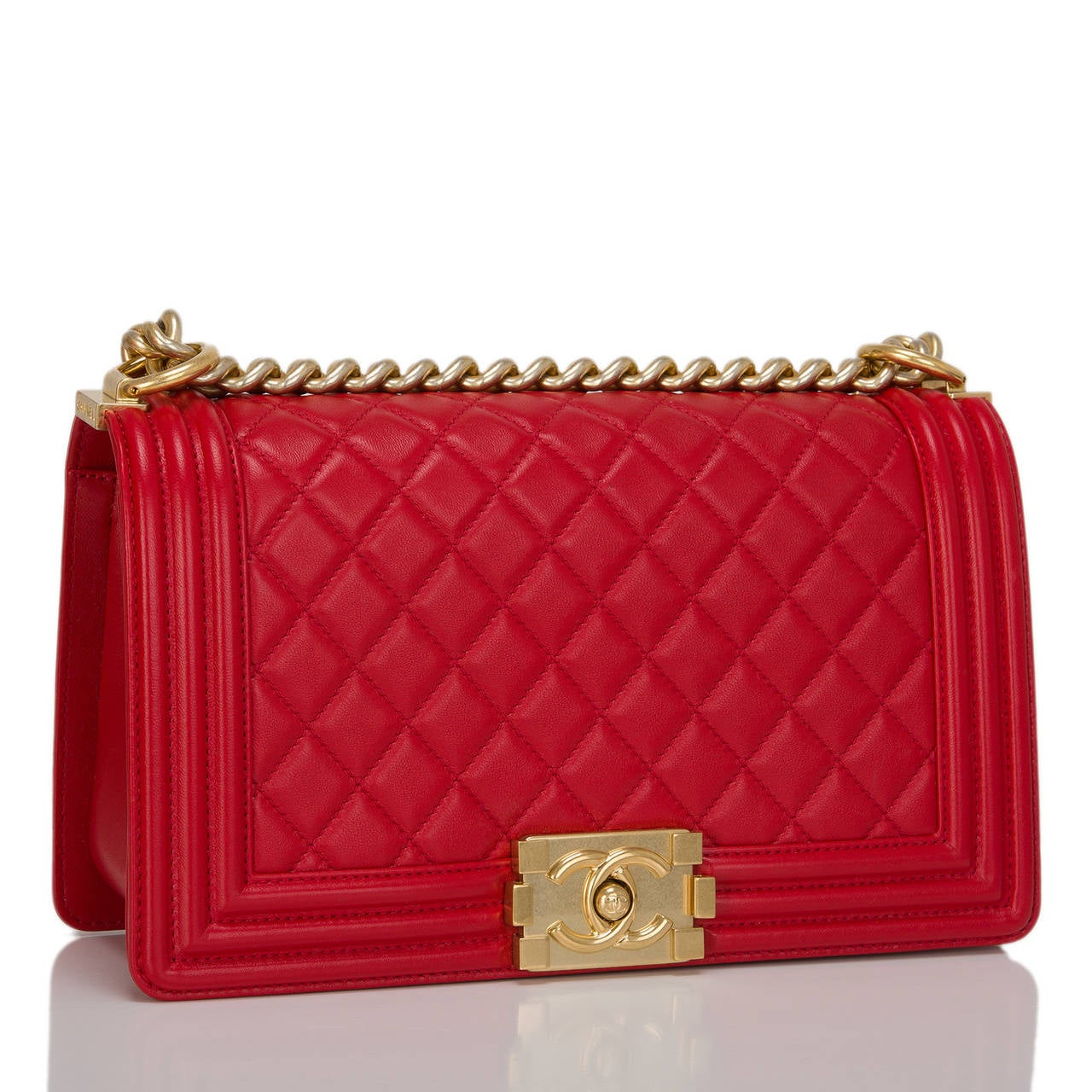 Chanel red quilted lambskin Medium Boy Bag with aged gold tone hardware. This bag features a full front flap with the Boy Chanel signature CC push lock closure and aged gold tone chain link and red leather padded shoulder/crossbody strap.  The