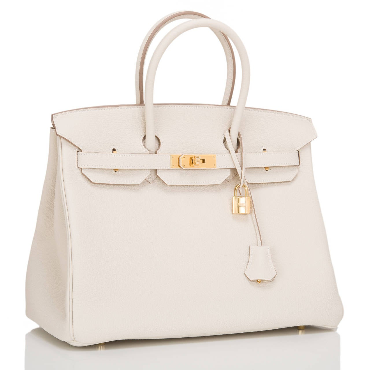 This Hermes Craie 35cm in togo leather with gold hardware.  This Birkin features tonal stitching, front toggle closure, clochette with lock and two keys, and double rolled handles. The interior is lined in Craie chevre with one zip pocket with an
