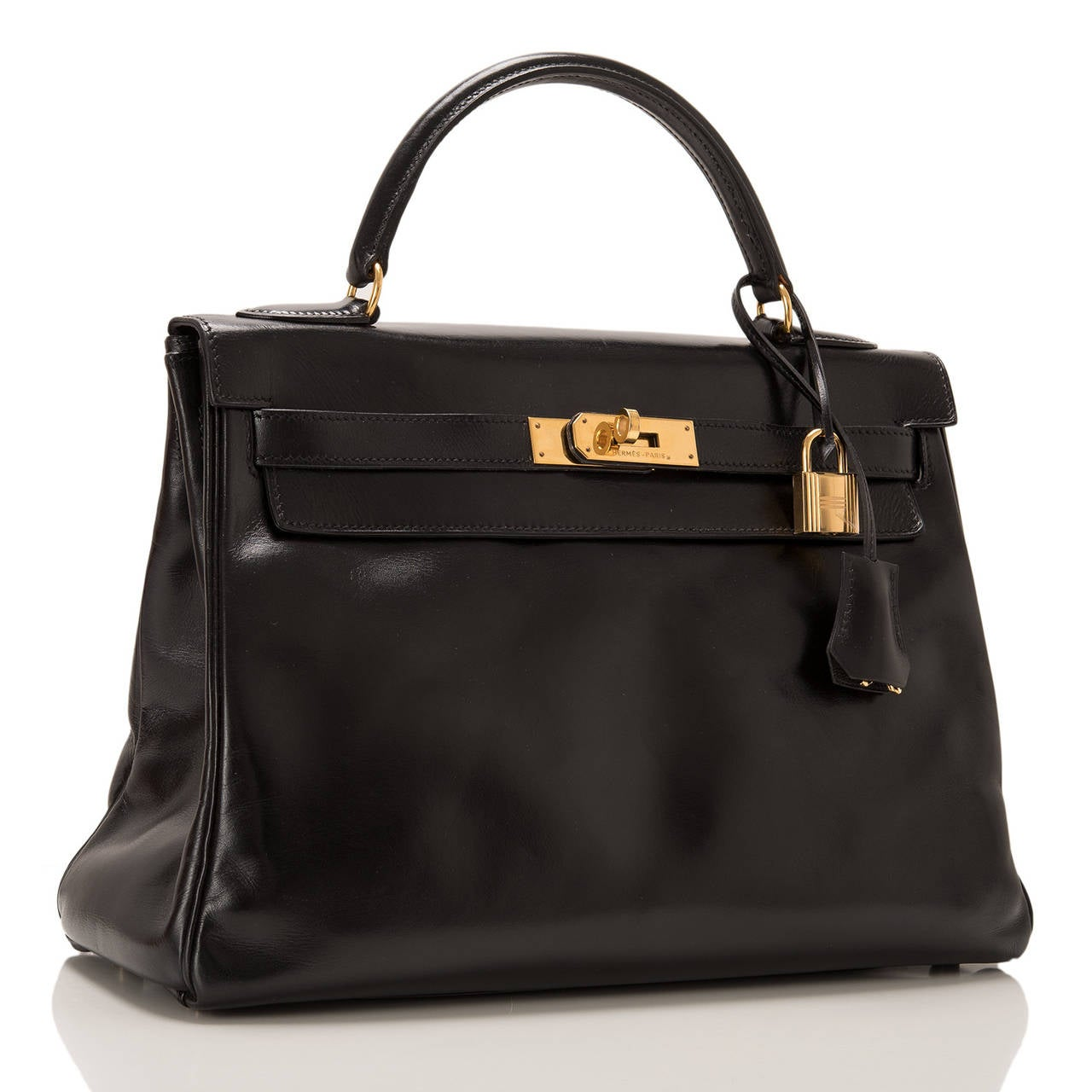 Hermes Black Kelly 32cm in box calf leather with gold hardware.  This Kelly features tonal stitching, front toggle closure, a clochette with lock and two keys and a single rolled handle. The interior is lined in Black chevre and features one zip