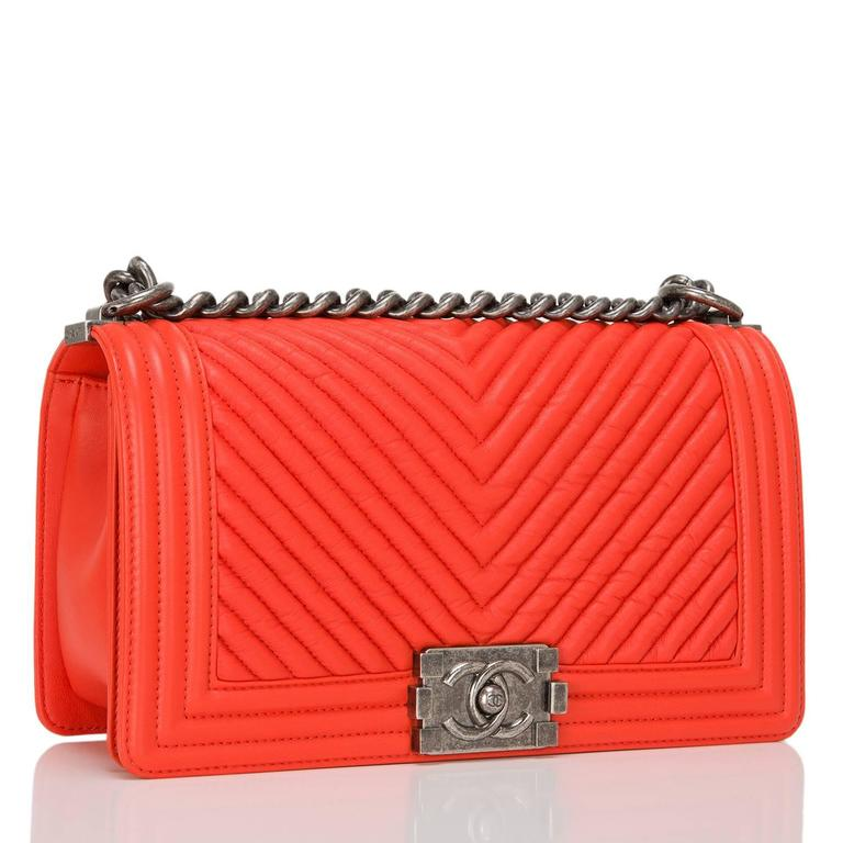 Chanel orange chevron quilted calfskin Medium Boy Bag with aged ruthenium hardware.  This bag features a full front flap with the Boy Chanel signature CC push lock closure and aged ruthenium chain link and orange leather padded shoulder/crossbody