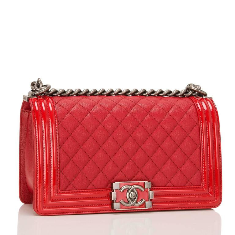 Chanel Medium Boy bag made of red goatskin (chevre) leather accented with patent leather trim and aged ruthenium hardware.  The bag features a full front flap with a limited edition Le Boy push lock CC closure in a glossy red lacquer and ruthenium