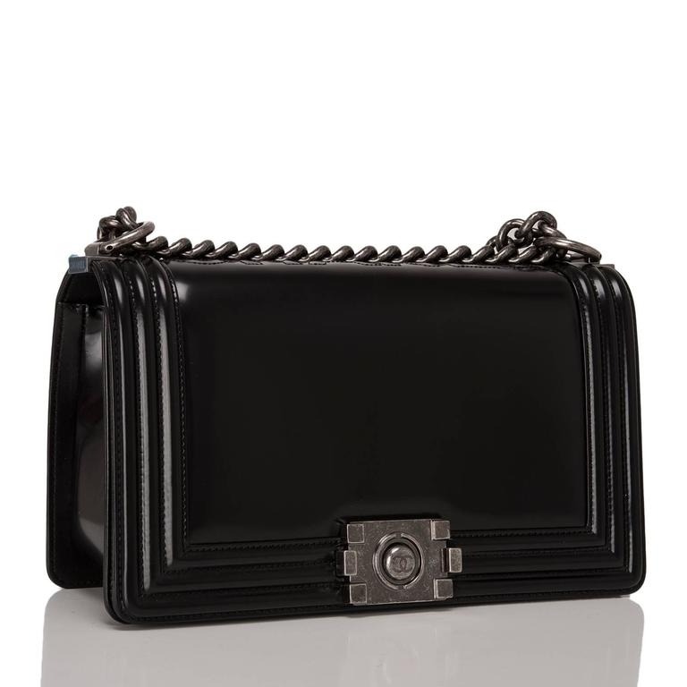 Chanel limited edition, Metiers D'Art Medium Boy bag is made of black smooth calfskin leather accented with aged ruthenium hardware.  The bag features a full front flap with a Le Boy CC logo push lock closure, C-H-A-N-E-L embossed at the spine and