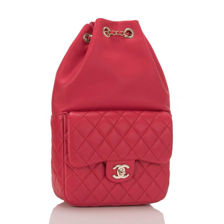 Chanel red flap backpack made of lambskin leather and accented with light gold tone hardware;  This bag features a front quilted leather flap pocket with signature CC turnlock closure, a top cinch closure and interwoven light gold tone chain link