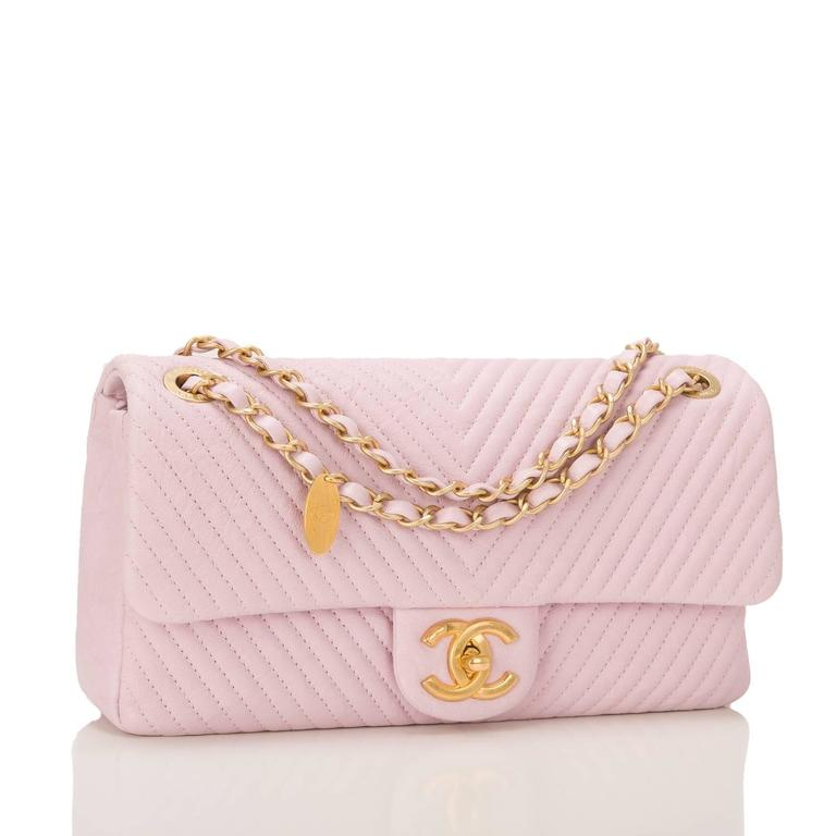 This Chanel light pink Chevron Medium Flap bag is made of distressed lambskin leather in a quilted chevron pattern and accented with antique gold tone hardware.