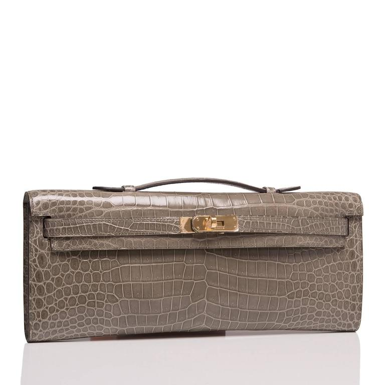 Hermes Gris Tourterelle (Gris T) shiny porosus crocodile Kelly Cut with gold hardware.  This Kelly Cut has tonal stitching, front straps with toggle closure and a top flat handle.  The interior is lined in Gris T chèvre leather and features an
