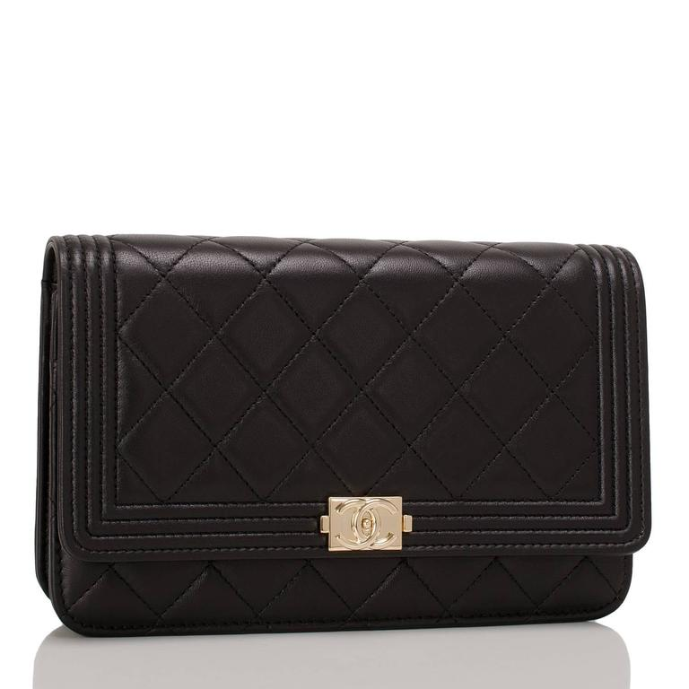Chanel black quilted lambskin leather Le Boy Wallet on Chain (WOC) with light gold tone hardware.  This WOC features a front flap with the signature Le Boy CC charm and hidden snap closure, smooth leather gusseted sides, and light gold tone