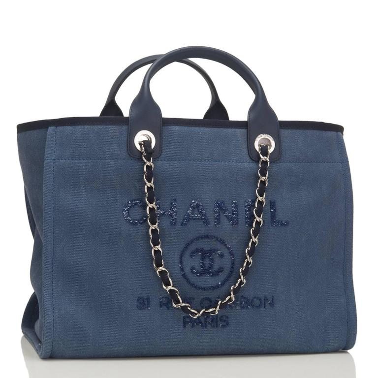 "Chanel Large Deauville Canvas Tote of navy canvas with navy sequin accents and silver tone hardware.  This bag features the signature CC logo in a circle with the brand CHANEL above it and the Paris flagship store address -- ""31 Rue Cambon Paris"" --"