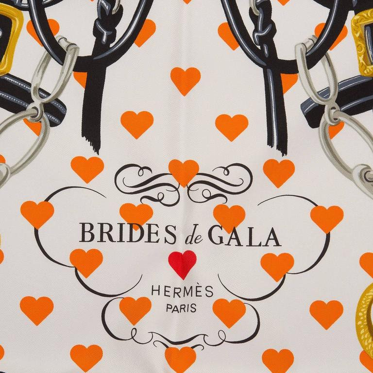 """Hermes limited edition """"Brides de Gala Love"""" silk twill scarf designed by Hugo Grygkar in a blue colorway.  This scarf features an equestrian motif on a white background with dark navy borders with blue hearts on the borders and orange hearts on the"""