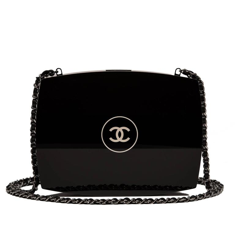 This Chanel Compact Powder Minaudière is made of black plexiglass with silver tone metal hardware.