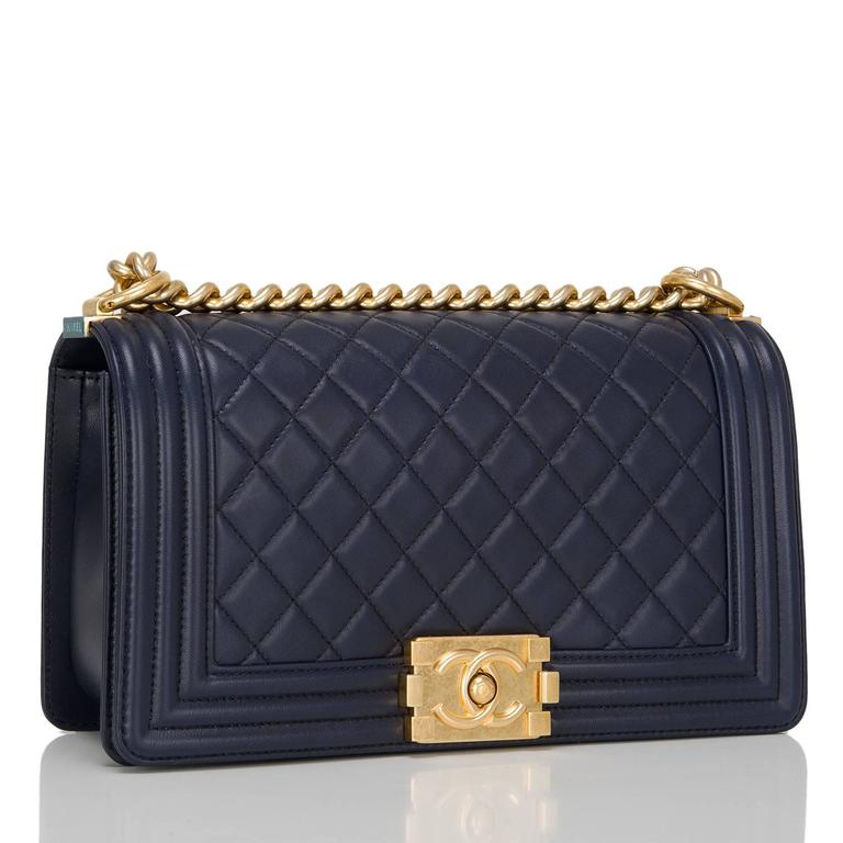 Chanel navy quilted calfskin Medium Boy Bag with aged gold tone hardware.  This Chanel bag features a full front flap with the Boy Chanel signature CC push lock closure and aged gold tone chain link and navy leather padded shoulder/crossbody