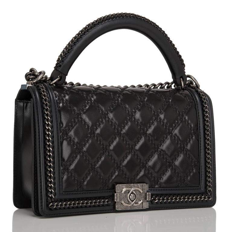 This Chanel New Medium Boy bag with a top handle is made of shiny goatskin leather and accented with aged ruthenium hardware.