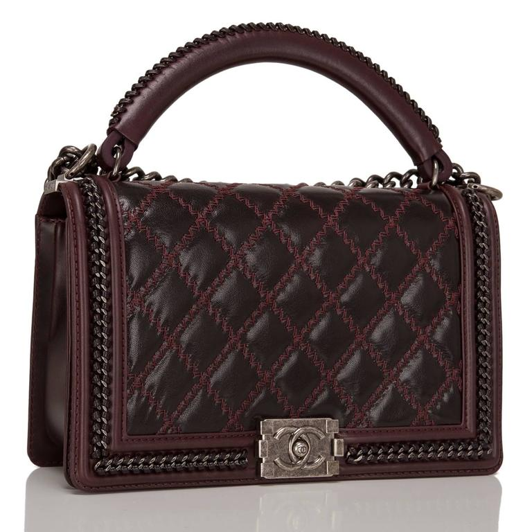 This Chanel limited edition New Medium Boy bag with a top handle is made of shiny goatskin leather and accented with aged ruthenium hardware.  The bag features a limited edition braided leather and chain top handle, a full front flap with the