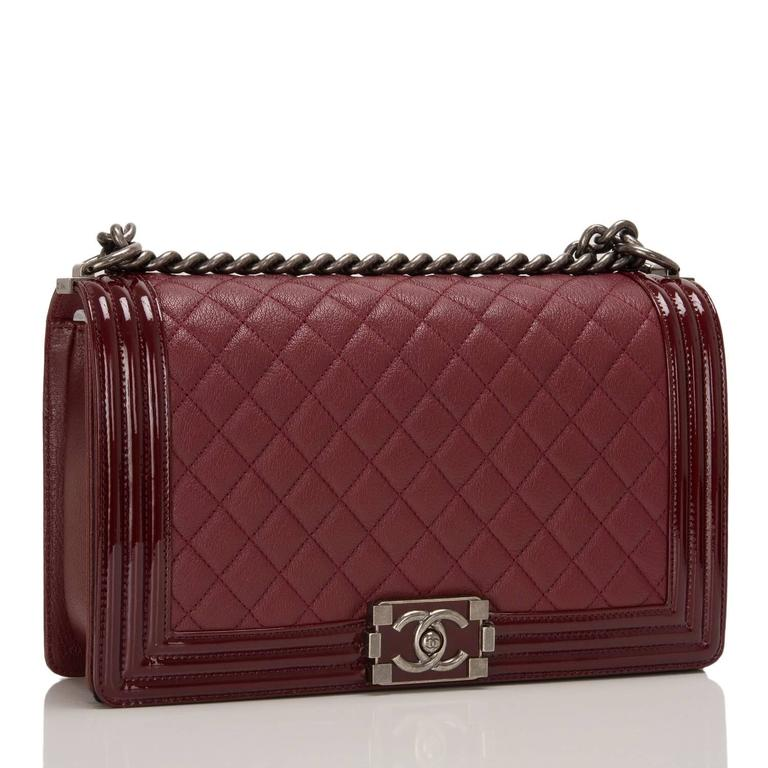 This Chanel New Medium Boy bag is made of burgundy quilted goatskin leather and accented with patent leather trim and aged ruthenium hardware.  The bag features a full front flap with a unique CC logo closure in a lacquered gloss, patent leather