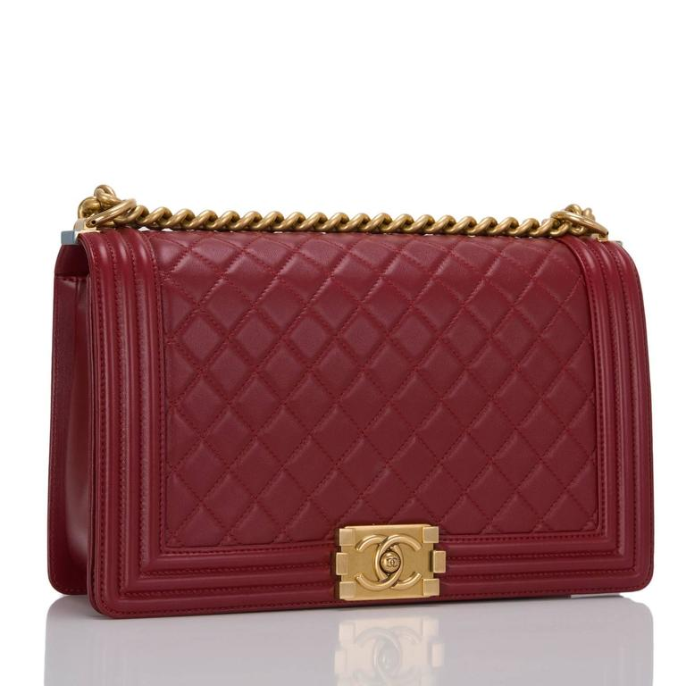 This New Medium Boy bag is made of dark red lambskin leather and accented with antique gold hardware.