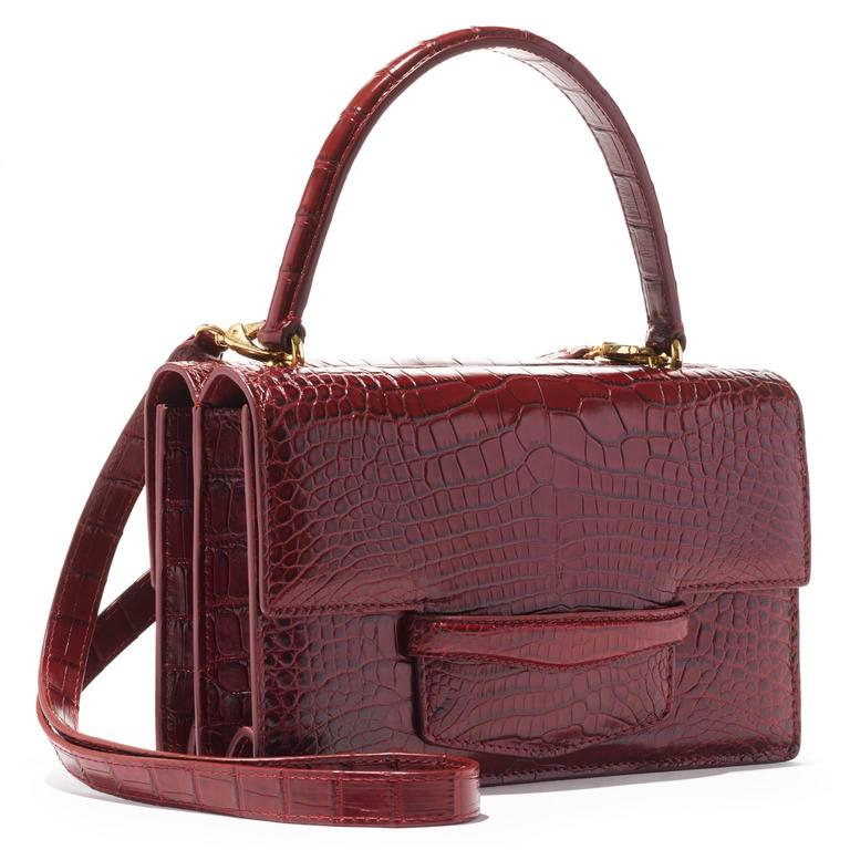 """This double gusseted alligator bag is fully lined in leather. A stitched doubled sided handle is joined to the bag with interlocking gold rings. There is an additional 40"""" detachable shoulder strap.   - one exterior pocket in center of the bag"""