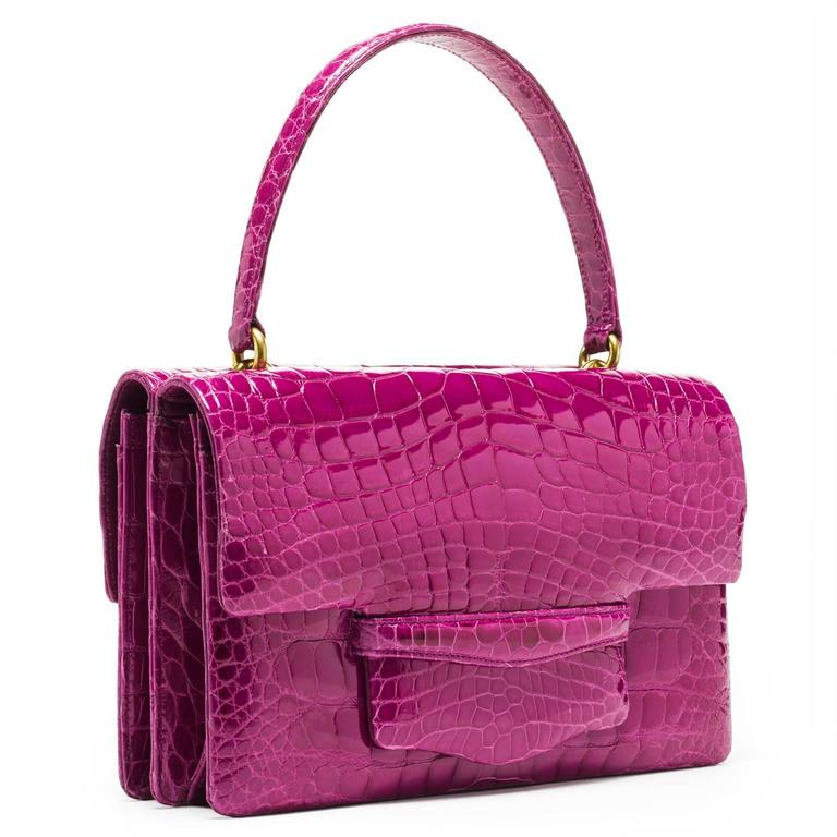 This double gusseted alligator bag is fully lined in leather. A stitched doubled sided handle is joined to the bag with interlocking gold rings. 