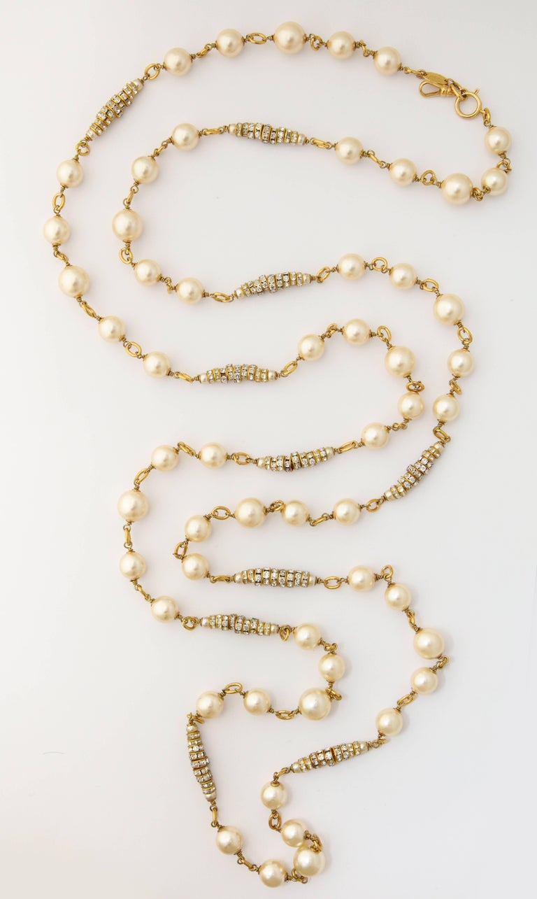 A wonderful long necklace by Chanel with faux natural pearls on a long chain with several rhinestone clusters. It can be worn doubled and triple up.