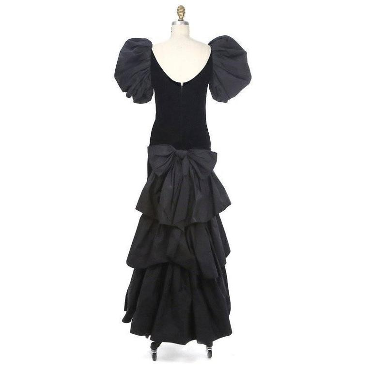 This is a haute couture gown in black velvet by Yves Saint Laurent, circa 1980s. It features a puffed short sleeve and a volumunus tiered train.  Other details include a detachable bow at the back waist, high neckline with a scooped back, and a
