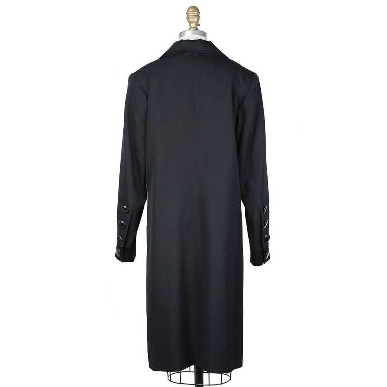 This is a tuxedo dress by Yves Saint Laurent from 1993.  Details include high lapels and 4-side front pockets.  The closures include three pockets and 4 buttons on the sides of sleeves.