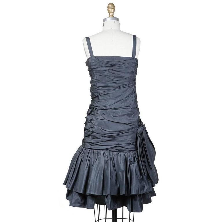 This is an haute couture dress by Yves Saint Laurent c. 1980s.  It is made from charcoal colored satin. It features gathered and folded fabric all around with a two tiered ruffled skirt. Other details include a bow at the side and half inch wide