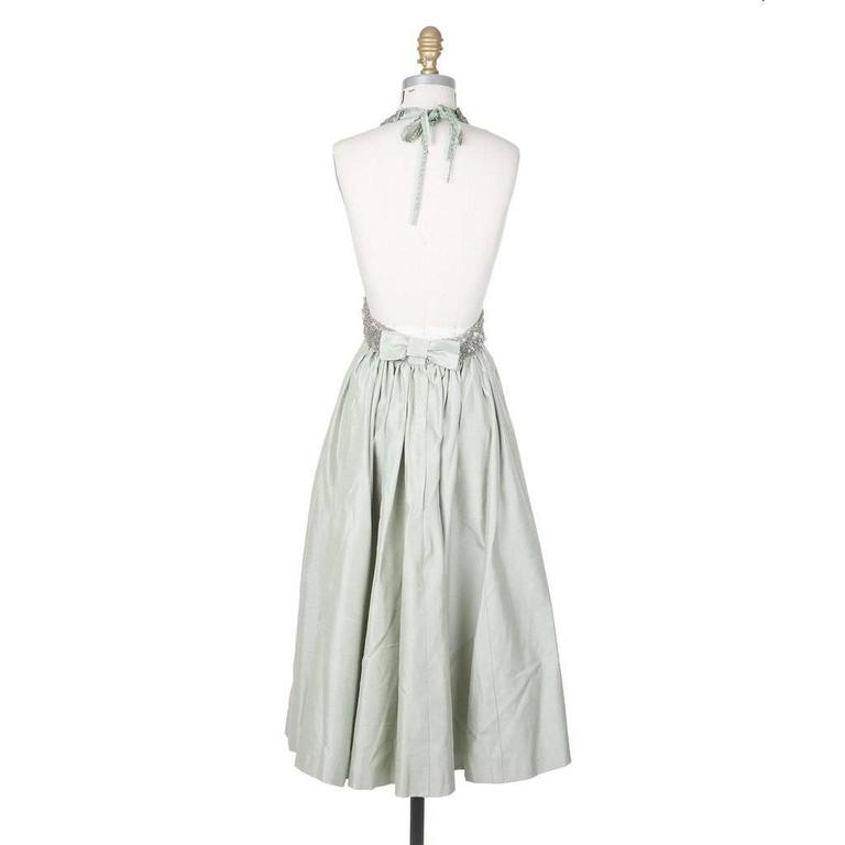 This is a mint colored halter dress by Jacques Fath c. 1980s.  It features a bodice embellished with a combination of beads, sequins, and paillettes.  The tea length skirt is constructed from a subtly textured mint green silk and is lined in satin.
