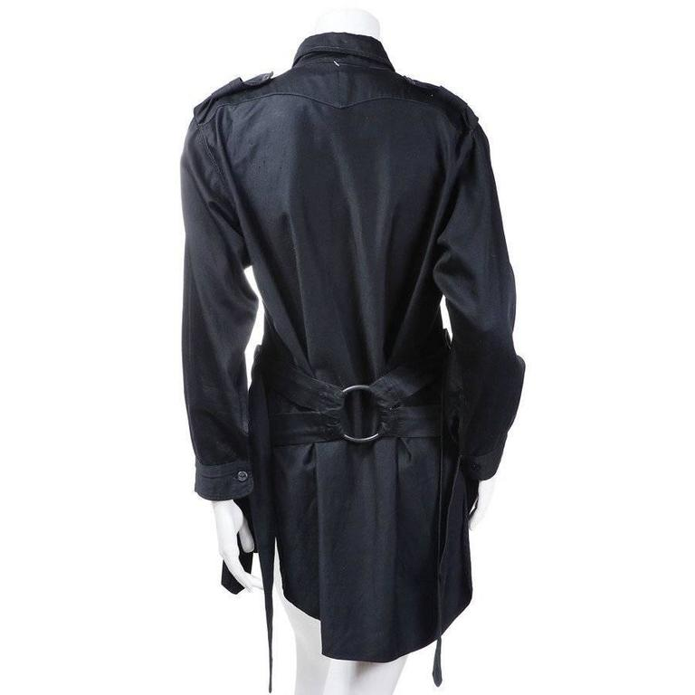 This is a shirt from 1976 by Vivienne Westwood for Malcolm McLaren.  It is a black pullover shirt with a button up polo style neckline and two shoulder tabs.  The jacket features adjustable bondage straps that are bound by two rings, one in the