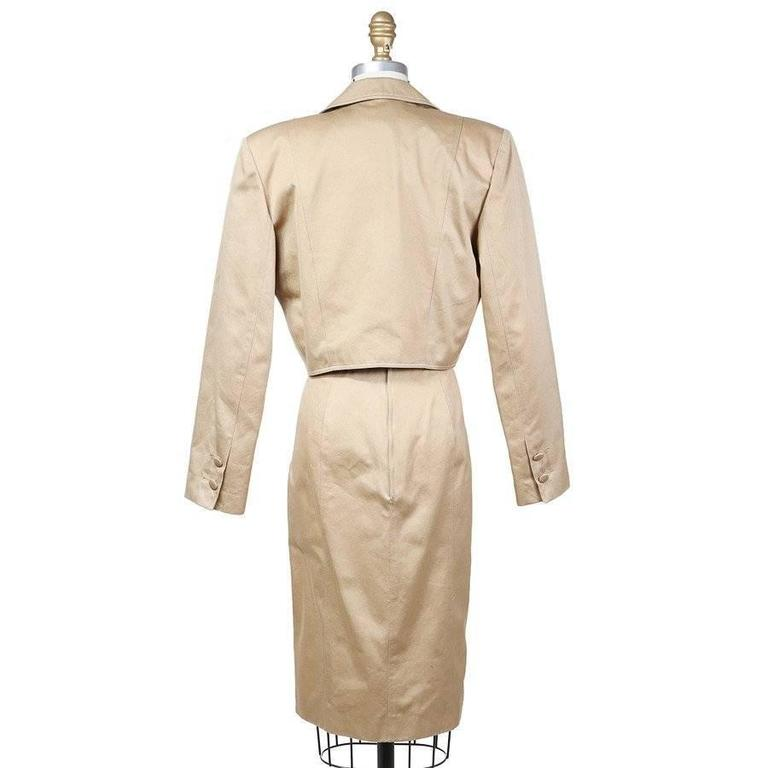 This is a beige strapless dress and jacket set by Patrick Kelly c. 1980s.  The dress features a corset with shoe string lacing, a sweetheart neckline, and a v shaped seam at the waist.  The cropped jacket has a matching lace up detailing, a lapel