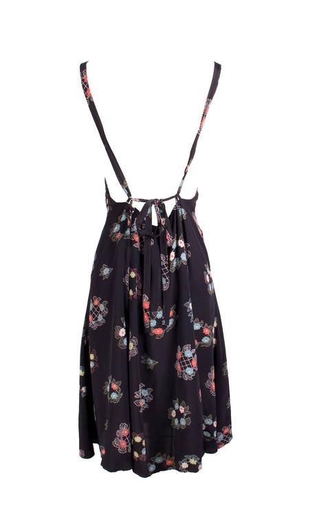 This is a silk chiffon dress by Ossie Clark c. 1970s.  It features a floral print by Celia Birtwell. Details include halter straps and a cinching back tie. There is also a hidden zipper down the center back.