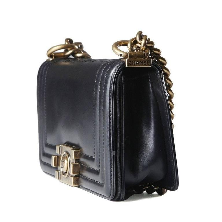 This is a black leather 1st edition Le Boy bag by Chanel from 2012.  It features antique gold hardware, a leather and chain shoulder strap, and a flap closure. The flap has a decorative squeeze lock.  Other details to note are the triple ribbed