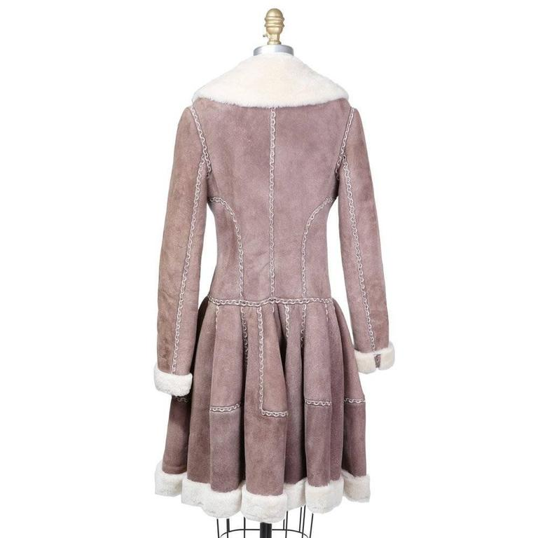 This is a suede shearling coat by Azzedine Alaia from the past 5-10 years.  It features interlocking curved cut detail on seams, long full skirt (cut like a circle skirt), and hidden string tie around waist.  It has a shearling lining, collar, and