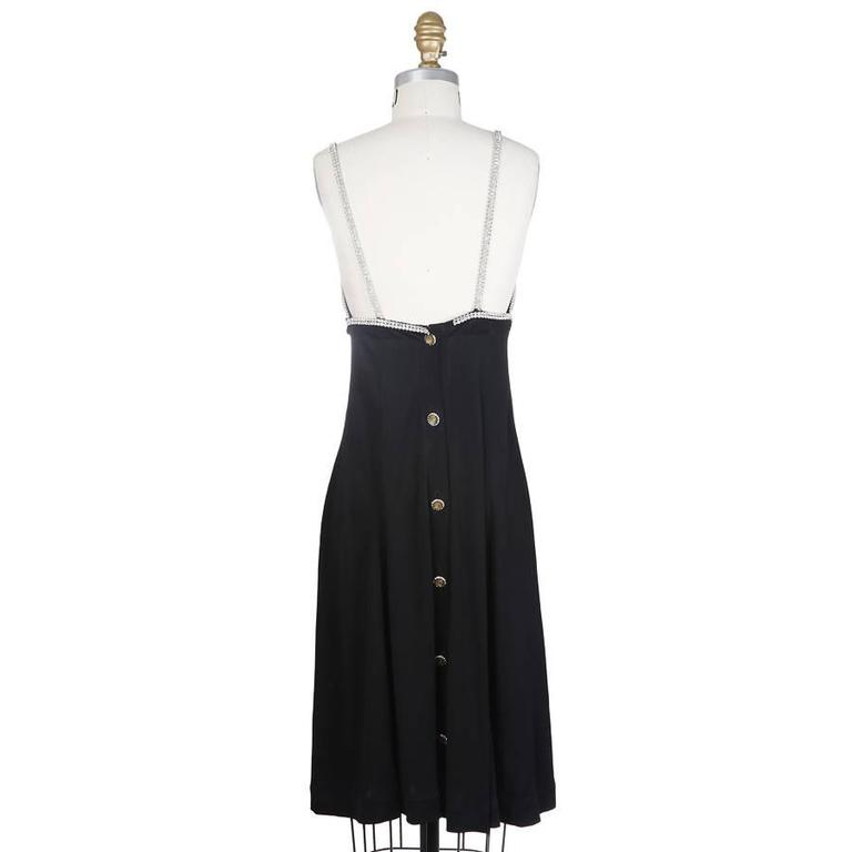 This is a baby doll dress by Todd Oldham from spring 1995.  It is made of a heavy black silk and features jewel straps and trim around the bust.  The closure is six large jewel and stone buttons down the back with a hook and eye closure at the top.